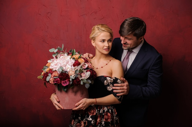 Man hug his woman with the bouquet of flowers Premium Photo
