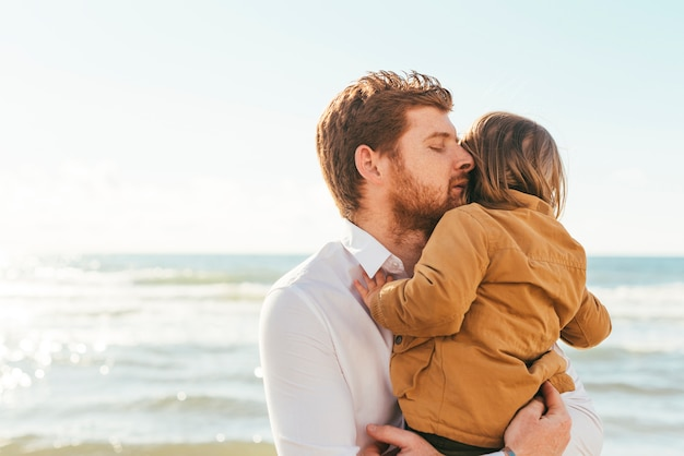 Man hugging child on seashore Free Photo