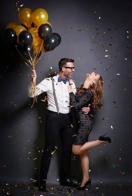 Мужчина обнимает свою танцующую жену на вечеринке Бесплатные Фотографии