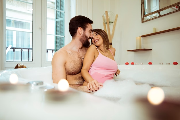 Man hugging smiling woman in spa tub with water and foam Free Photo