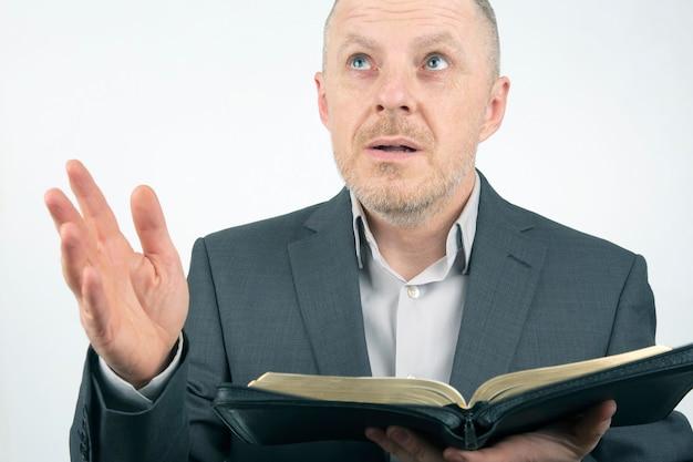 남자 비즈니스 정장에 성경을 읽고 있습니다. 프리미엄 사진