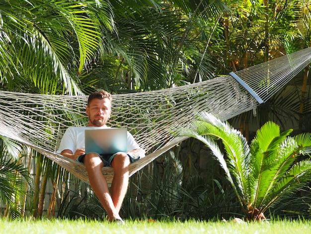 Человек в отеле летом с ноутбуком лежал в гамаке Premium Фотографии