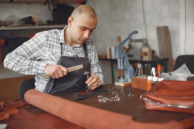 Человек в студии создает изделия из кожи Бесплатные Фотографии
