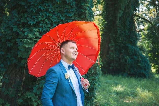 Мужчина в костюме с красным зонтом в парке Premium Фотографии