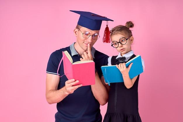 Человек в академической шляпе, держа книгу, учиться вместе с милой предподростковый девушка в школьной форме. отец, дочь, изолированных на розовом пространстве в. любовь, семейный день, концепция детства Premium Фотографии