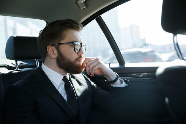Человек в очках сидит на заднем сиденье автомобиля Бесплатные Фотографии