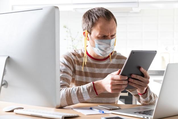 耳に麺が入ったフェイスマスクの男が、タブレットで偽のニュースを読む Premium写真