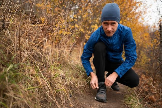 Человек в лесу завязывает шнурки Бесплатные Фотографии