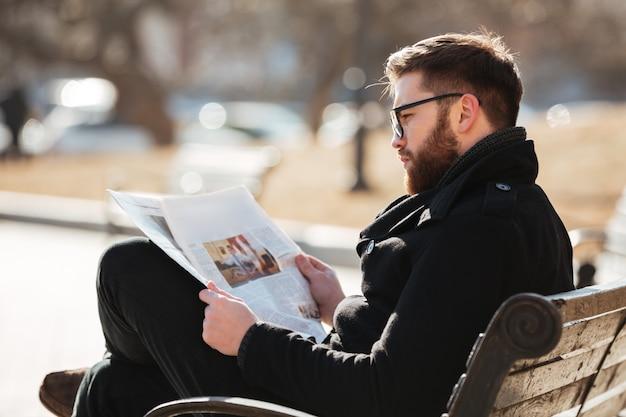 座っていると都市で新聞を読んでメガネの男 無料写真