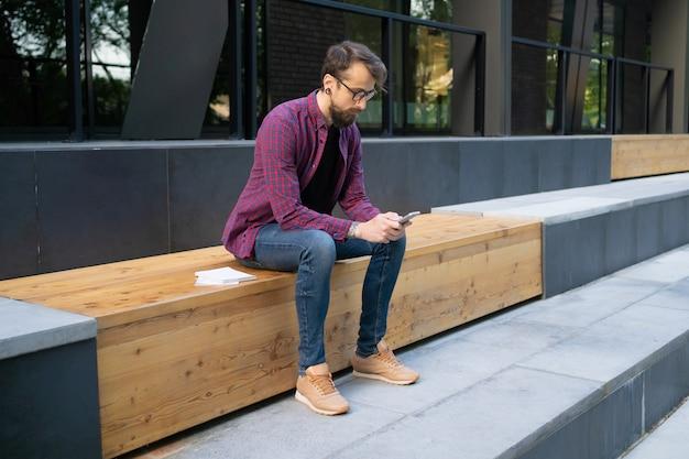 電話で木製のベンチに座っているガラスの男 無料写真