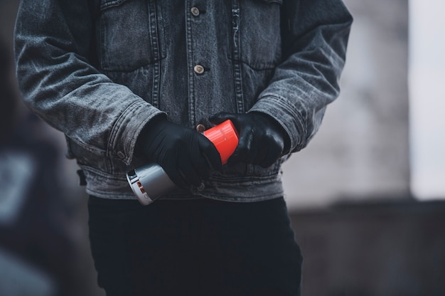 Мужчина в перчатках и джинсовой куртке берет аэрозольную краску. серые дни работы художников-граффити Premium Фотографии