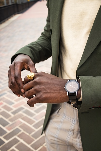 金色のライオンリングと時計を身に着けている緑のブレザーの男 無料写真
