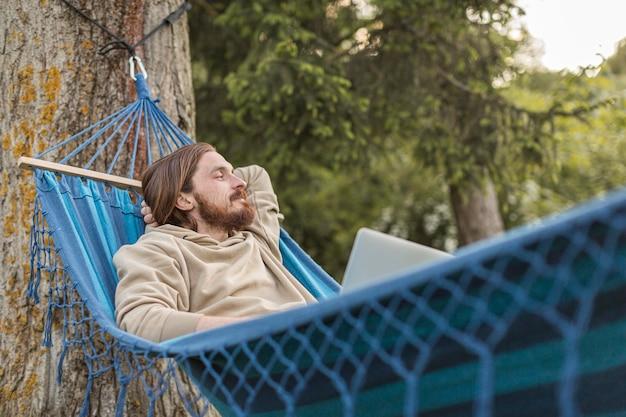 Человек в гамаке, наслаждаясь природой с ноутбуком Бесплатные Фотографии