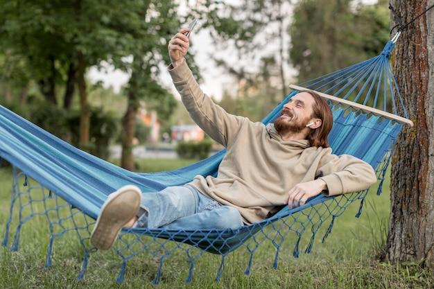 Человек в гамаке, принимая селфи с смартфон Бесплатные Фотографии