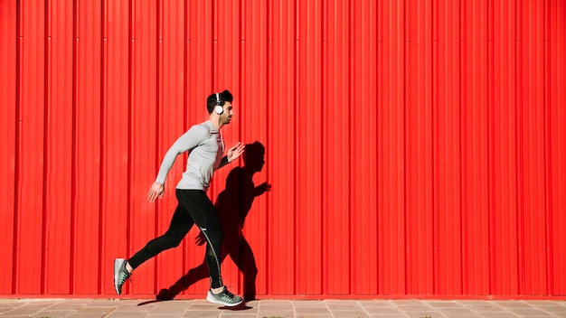 Man in headphones running near red walll Free Photo