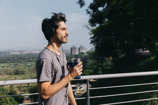 Man in headphones with thermocup at handrail Free Photo