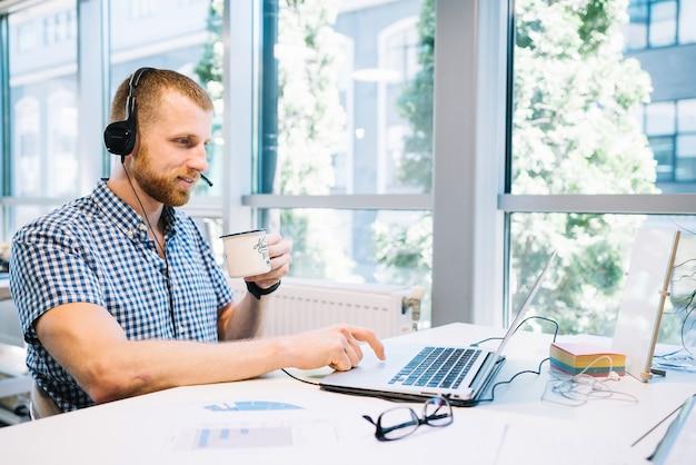 Man in headset working on laptop Free Photo