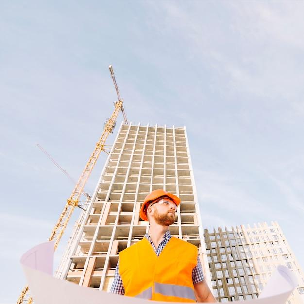 Man in helmet holding blueprint Free Photo