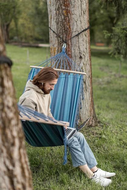 Человек в природе, сидя в гамаке и работает на ноутбуке Бесплатные Фотографии