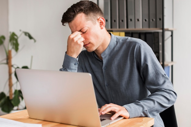 Человек в офисе во время пандемии испытывает головную боль Бесплатные Фотографии
