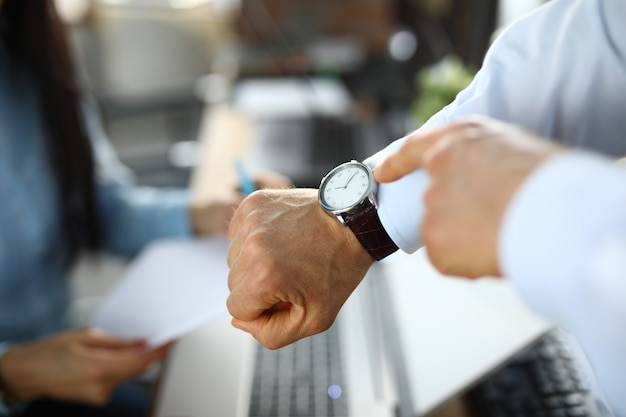 Человек в офисе показывает пальцем на часы Premium Фотографии