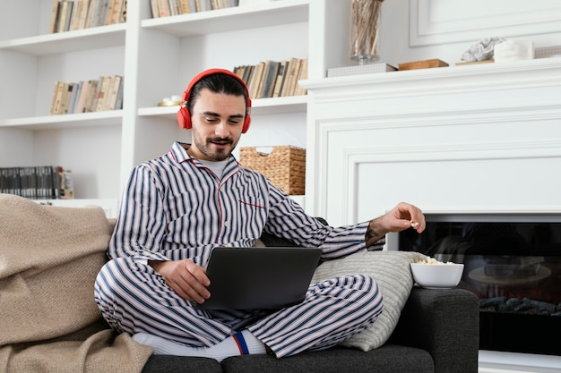 노트북에서 즐거운 시간을 보내고 잠 옷에있는 남자 무료 사진