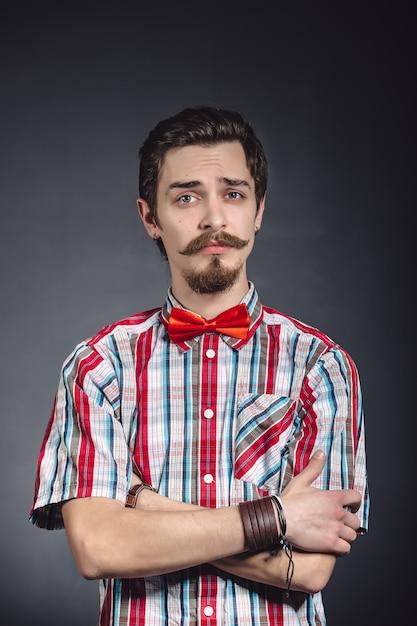 Человек в клетчатой рубашке и галстуке-бабочке в студии Бесплатные Фотографии