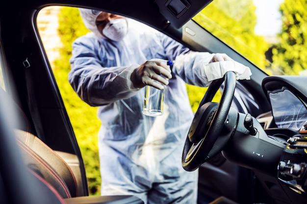 Человек в защитном костюме с маской дезинфицирует внутри автомобиля, протирает чистые поверхности, к которым часто прикасаются, предотвращает заражение коронавирусом, заражение микробами или бактериями. инфекция Premium Фотографии