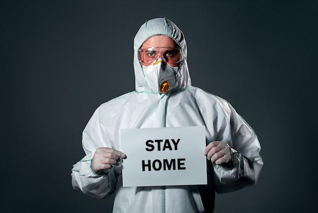 보호용 흰색 작업복을 입은 남자, 마스크와 안경, 종이 한 장, Stay Home 비문. 프리미엄 사진