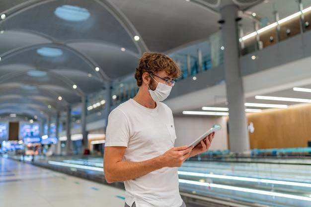 인공 호흡기 마스크를 쓴 남자가 공항에서 다음 비행기를 기다리고 태블릿을 사용하고 있습니다. 무료 사진