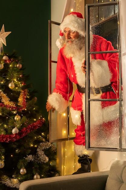 Человек в костюме санта попадает в дом через окно Premium Фотографии