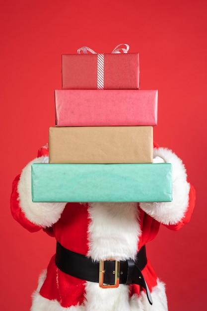 Человек в костюме санта-клауса с подарками Premium Фотографии