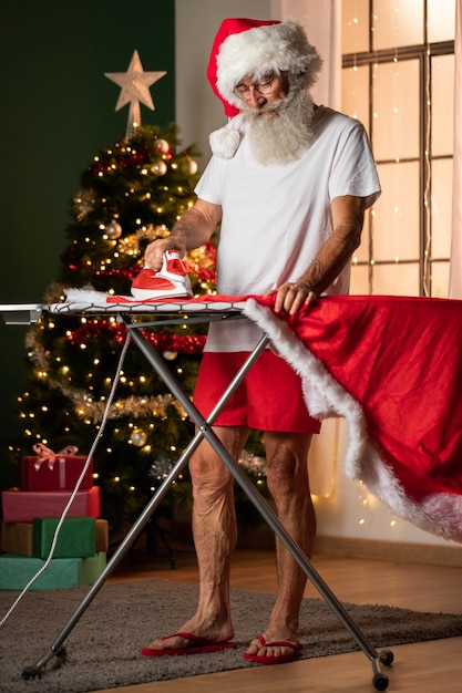 アイロン台を使用してサンタの衣装を着た男 無料写真