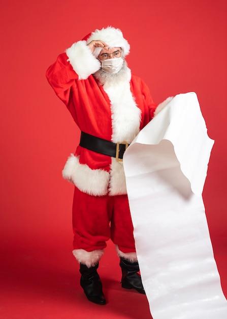 Мужчина в костюме санта-клауса с медицинской маской держит список подарков Бесплатные Фотографии