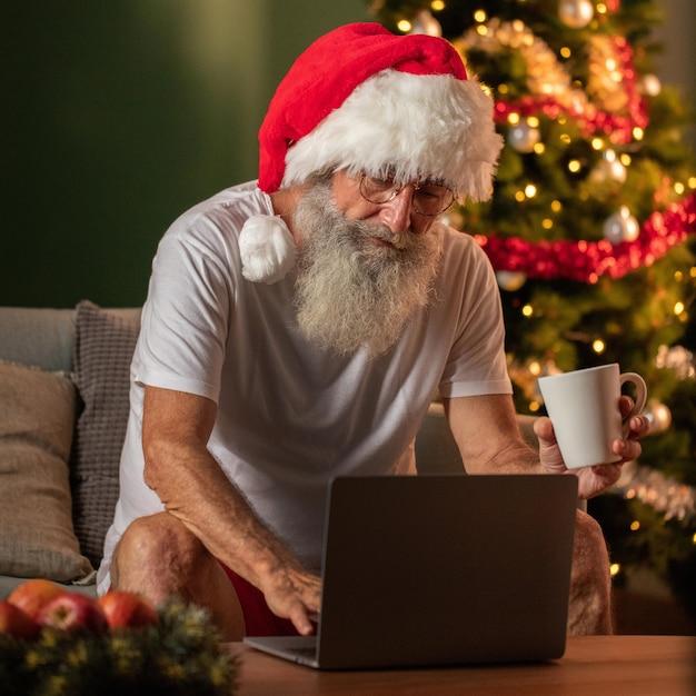 Человек в шляпе санта-клауса держит кружку и использует ноутбук дома Premium Фотографии