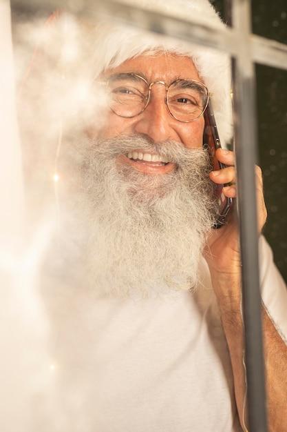 窓越しにスマートフォンで話しているサンタ帽子の男 無料写真
