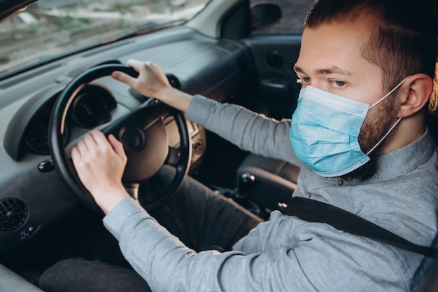 Человек в рубашке и медицинской маске сидит за рулем автомобиля. Premium Фотографии