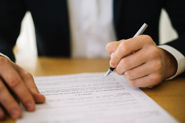 Man in suit signing contract Free Photo