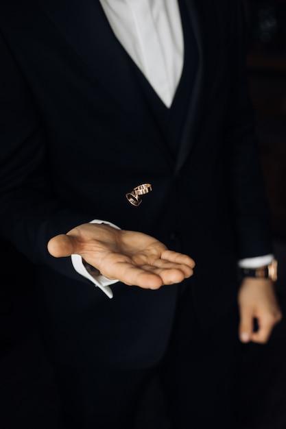 Мужчина в черном костюме бросает два обручальных кольца Бесплатные Фотографии