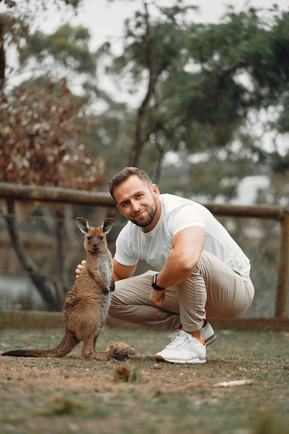 Человек в заповеднике играет с кенгуру Бесплатные Фотографии