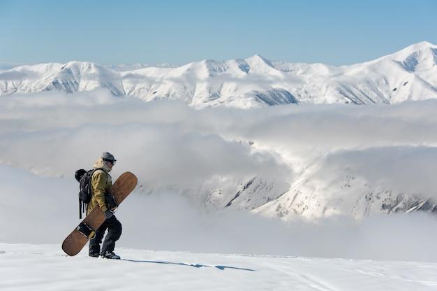 暖かいスキー用具の男はゆっくりと雪山をさまよう Premium写真