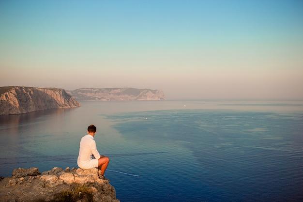 Человек в белом на открытом воздухе на краю обрыва наслаждаться видом на вершину горы рок Premium Фотографии
