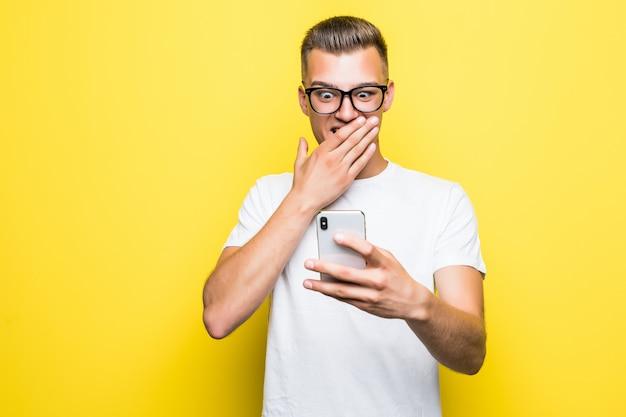 Мужчина в белой футболке и очках что-то делает на своем телефоне и делает селфи на желтом фоне Бесплатные Фотографии