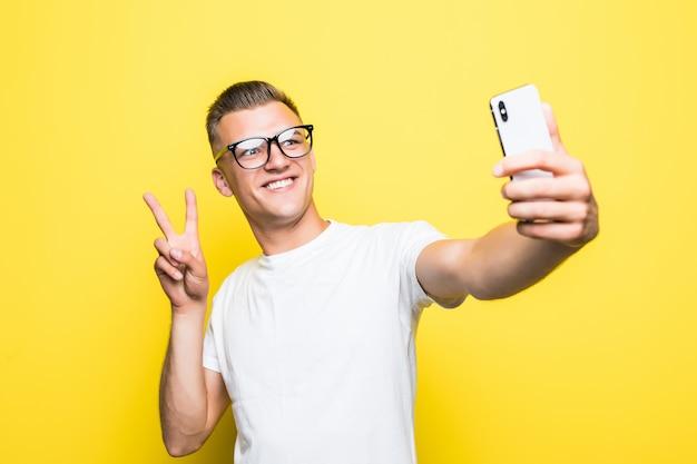 Мужчина в белой футболке и очках что-то делает на своем телефоне и делает селфи в знак победы Бесплатные Фотографии