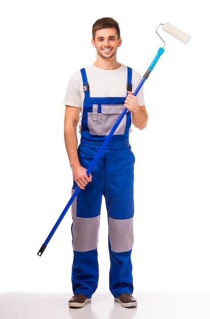 Человек в рабочей одежде, роспись стен в комнате. Premium Фотографии