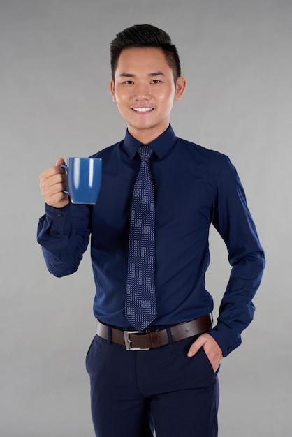 Man indark синий торжественная одежда, стоя на сером фоне с кружкой темно-синего чая Бесплатные Фотографии