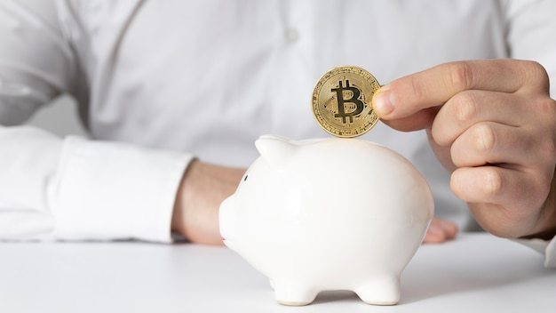Man inserting a bitcoin in a piggy bank Free Photo