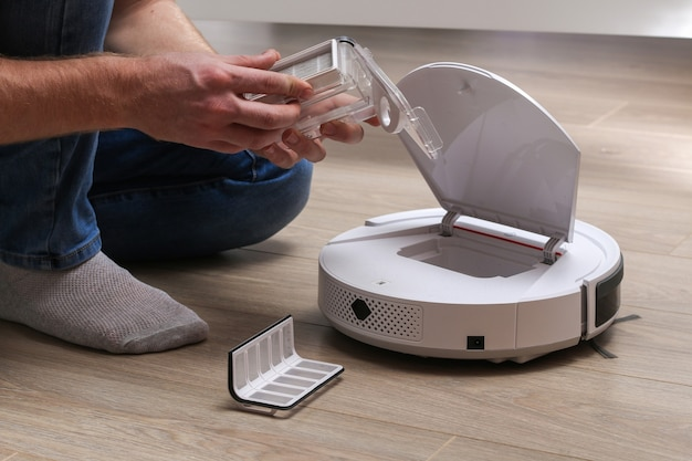 A man inserts a filter and a container to collect dust and debris into robot vacuum cleaner. Premium Photo
