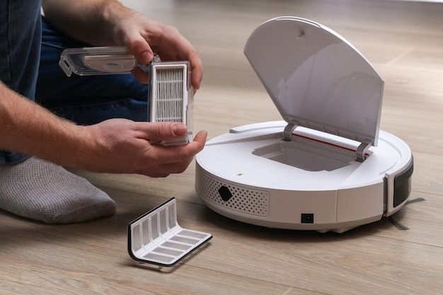 A man inserts a filter and a container to collect dust and debris into robot vacuum cleaner Premium Photo