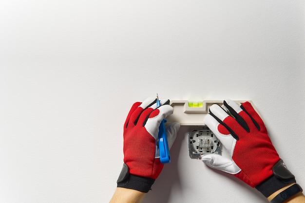 Мужчина устанавливает выключатель света после ремонта дома Premium Фотографии